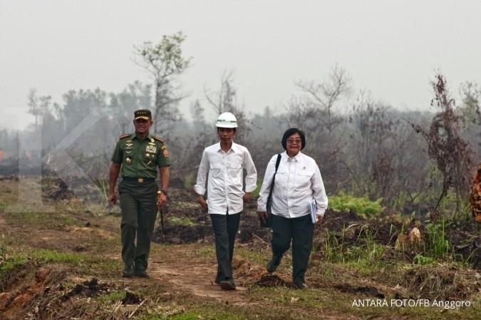 Presiden Joko Widodo (tengah) bersama Panglima TNI Jenderal Gatot Nurmantyo dan Menteri Lingkungan Hidup dan Kehutanan Siti Nurbaya saat meninjau penanganan kebakaran lahan di Desa Rimbo Panjang Kabupaten Kampar, Riau, Jumat (9/10). Presiden meminta penanganan untuk pencegahan kebakaran lahan dan hutan ke depan yang paling efektif adalah dengan memperbanyak sekat kanal dan embung penampung air. ANTARA FOTO/FB Anggoro/nz/15.